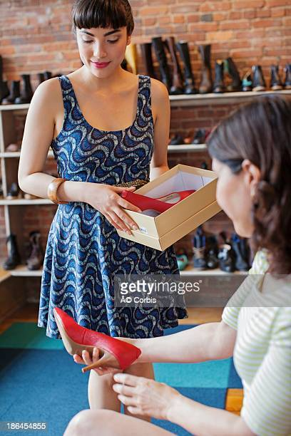 Woman in shoe store assisted by seller