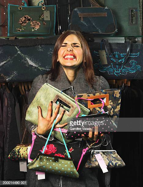 woman in shop clutching handbags, smiling - collection stock pictures, royalty-free photos & images