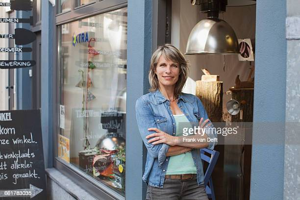 Woman in shop doorway, arms crossed looking at camera smiling