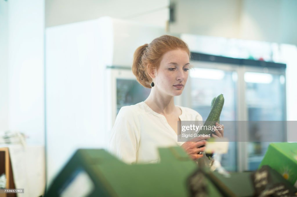 Woman in shop holding cucumber : Stock-Foto