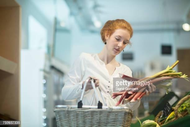 woman in shop holding shopping basket and rhubarb - sigrid gombert fotografías e imágenes de stock