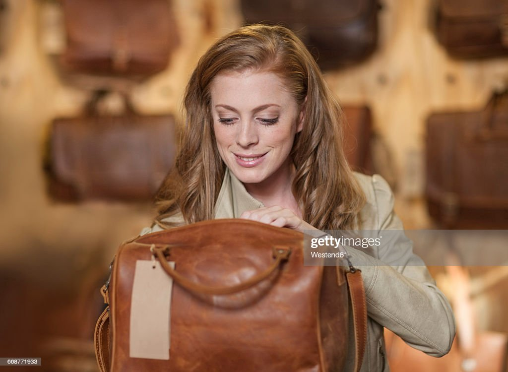 Woman in shop looking at leather bag : Stock Photo