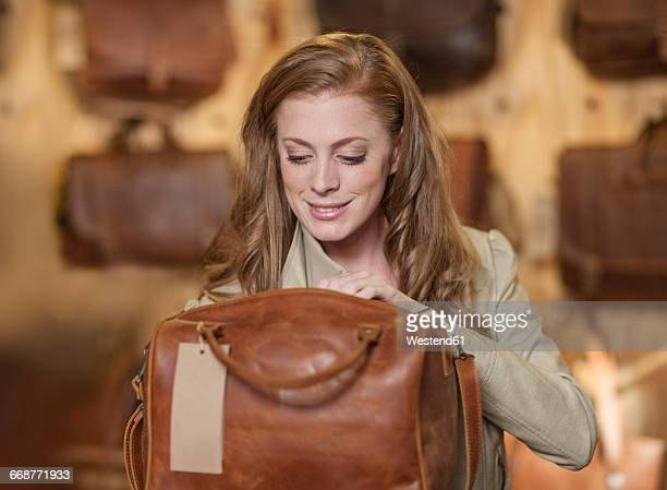 woman in shop looking at leather bag - leather purse stock pictures, royalty-free photos & images