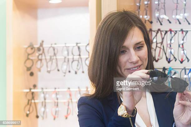 woman in shop looking at sunglasses smiling - sigrid gombert stock pictures, royalty-free photos & images