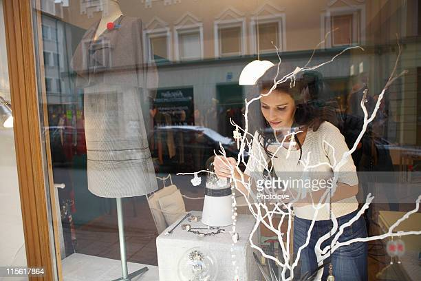 woman in shop window behind tree