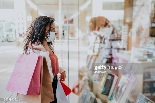 woman in shopping mall with bags shopping - merchandise stock pictures, royalty-free photos & images