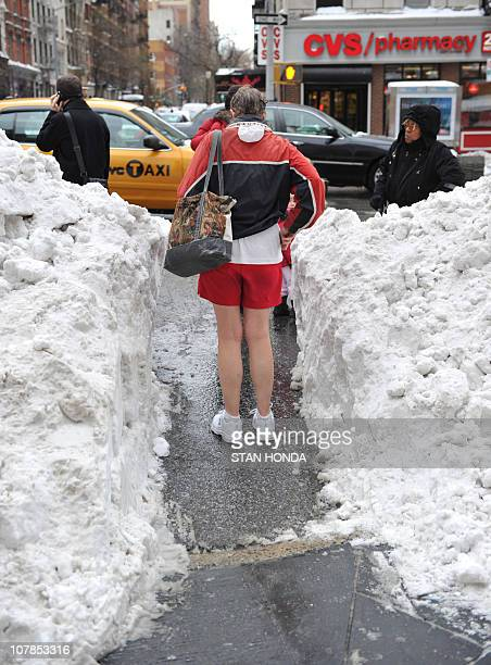 A woman in shorts stands in a path between snow drifts on Third Avenue on the east side of Manhattan in New York on December 28 one day after a...
