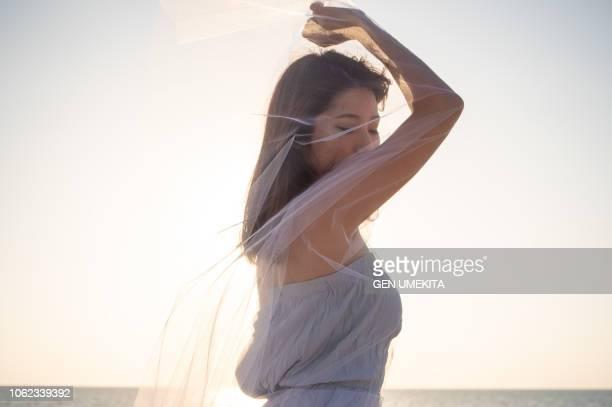 a woman in silhouette - doorzichtige stof stockfoto's en -beelden