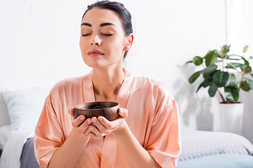 woman in silk bathrobe with wooden bowl in hands having tea ceremony in morning at home 978610500