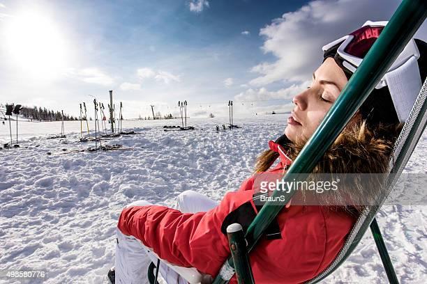 Frau im ski-wear entspannen Sie auf einem Liegestuhl im winter.