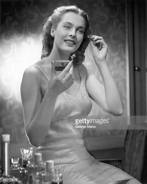 Woman in slip applying make-up
