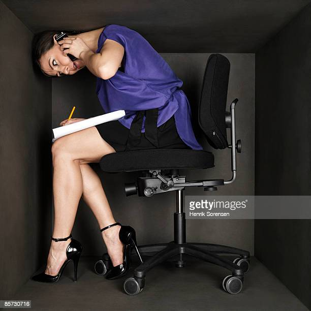 Woman in small black box working