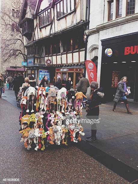 Woman in small business selling cute animal hats on high street in Oxford