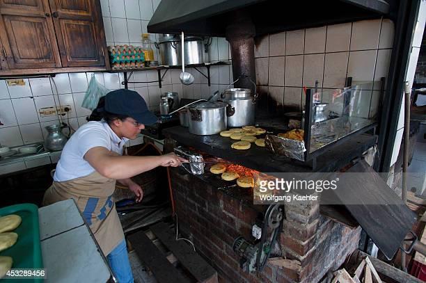 Woman in small roadside restaurant cooking Arepas in La Calera near Bogota Colombia
