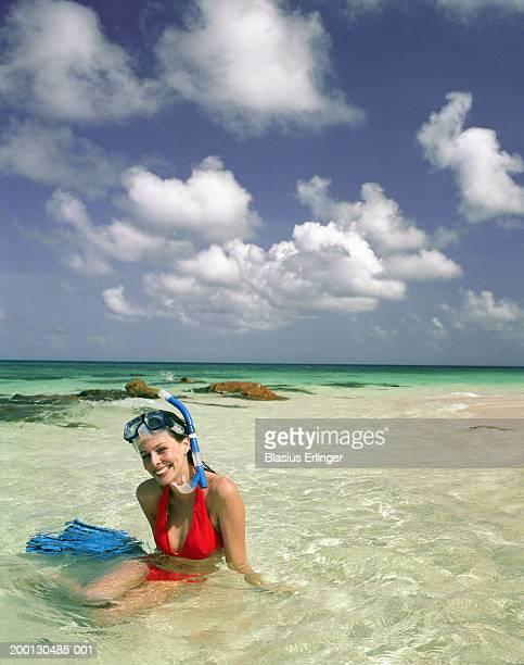 Woman in snorkeling gear sitting in ocean, portrait