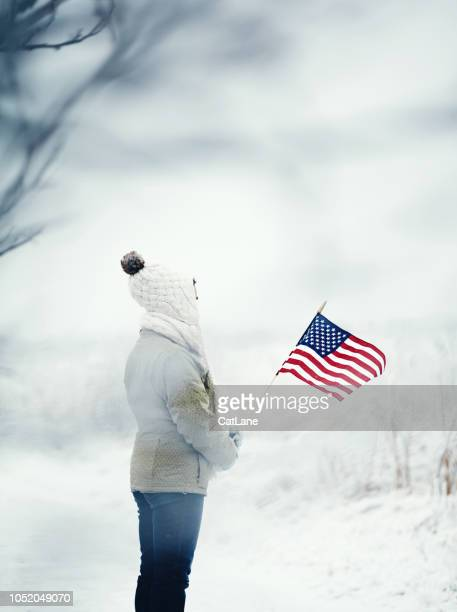 woman in snowy landscape holding american flag - patriotic christmas stock pictures, royalty-free photos & images