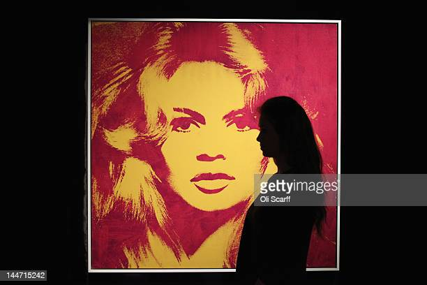 A woman in Sotheby's auction house views an artwork by Andy Warhol entitled 'Brigitte Bardot' with is expected to fetch 4 million GBP on May 18 2012...