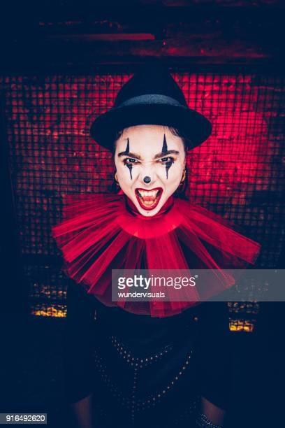woman in spooky evil clown costume and scary make-up - scary clown makeup stock photos and pictures