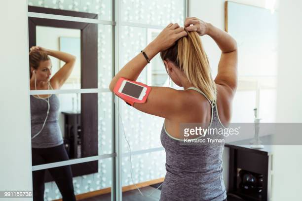 woman in sport clothing tying ponytail while looking in mirror at home - ponytail stock pictures, royalty-free photos & images