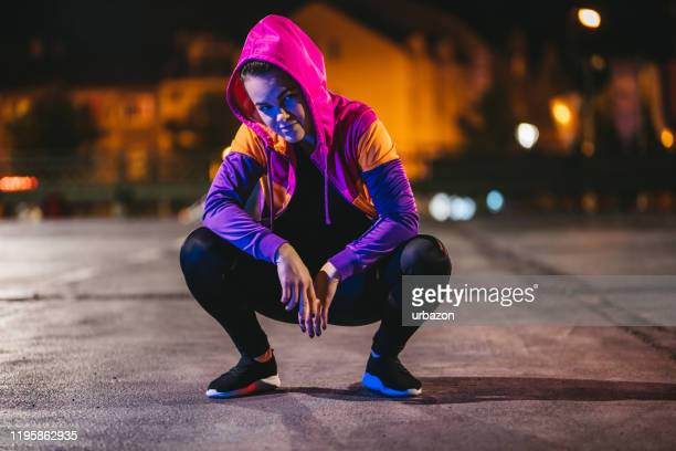woman in sport wear crouching - rap stock pictures, royalty-free photos & images