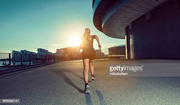 Woman in sports clothes runs towards the sun