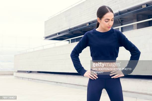 Woman in sports clothes with hands on hips