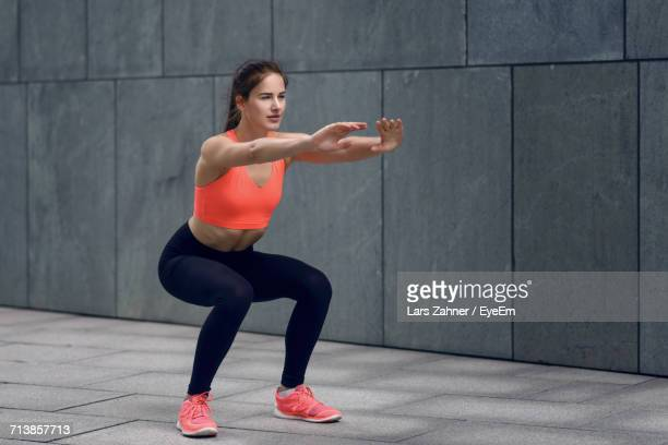 woman in sports clothing doing squats - hurken stockfoto's en -beelden