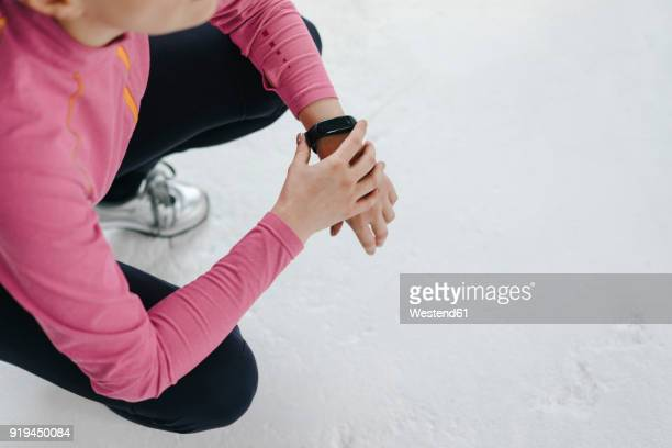 Woman in sportswear crouching wearing activity band