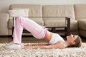 Woman in sportswear doing hip bridge exercise