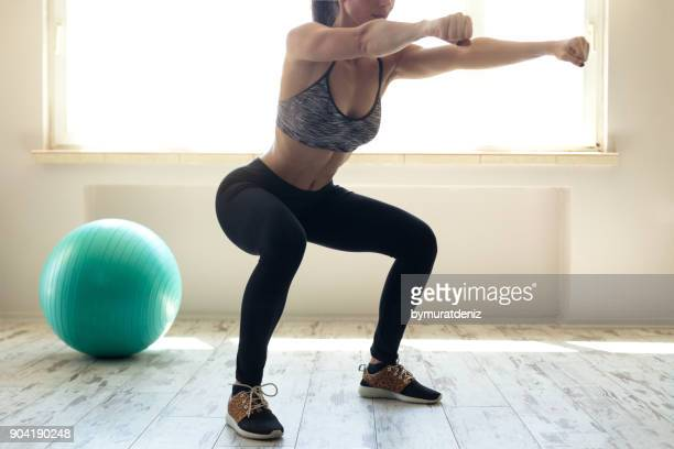 woman in sportswear doing squat - woman bum stock photos and pictures