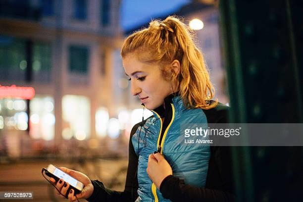 woman in sportswear listening music in city - junge frau allein stock-fotos und bilder