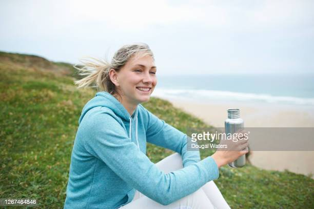 woman in sportswear sitting on atlantic coastline with plastic free water bottle. - one mid adult woman only stock pictures, royalty-free photos & images