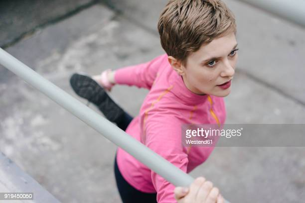 Woman in sportswear stretching at railing
