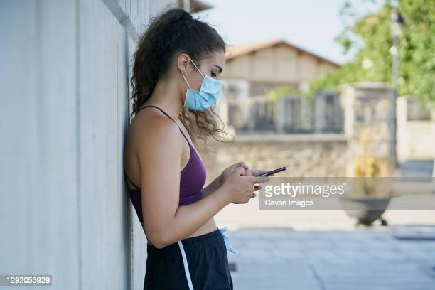 woman in sportswear wearing a medical mask looking at a smartphone - face guard sport stock pictures, royalty-free photos & images