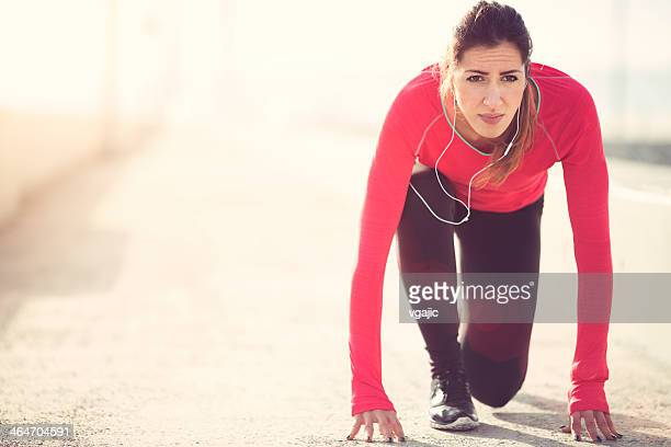 Woman in start position for running.