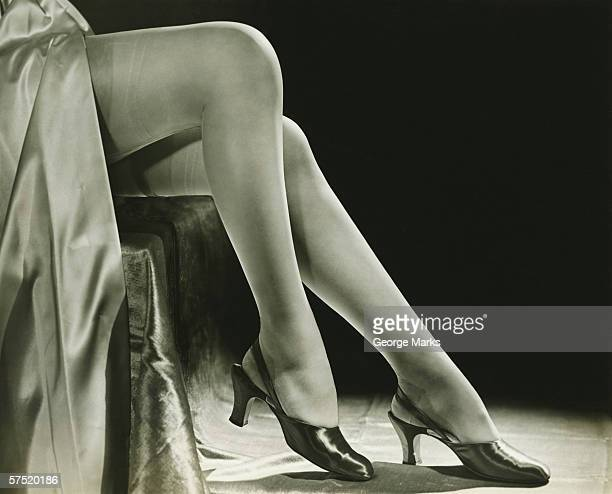 woman in stockings sitting on chair, close-up of legs, (b&w), low section - 1940s erotica stock photos and pictures