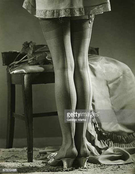 woman in stockings standing indoors, (b&w), low section - vintage stockings stock photos and pictures