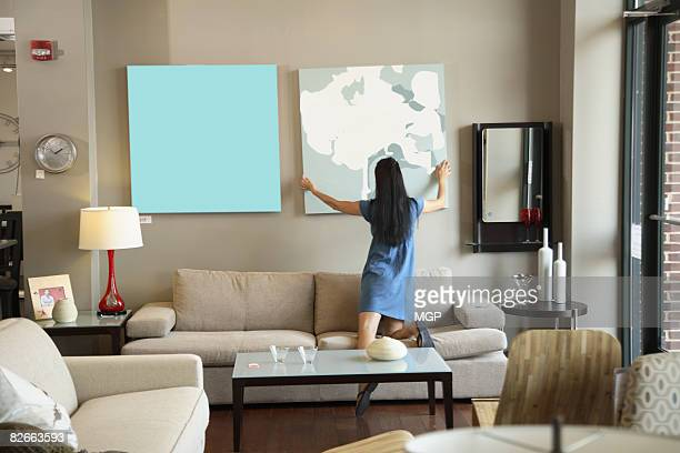 woman in store adjusting painting