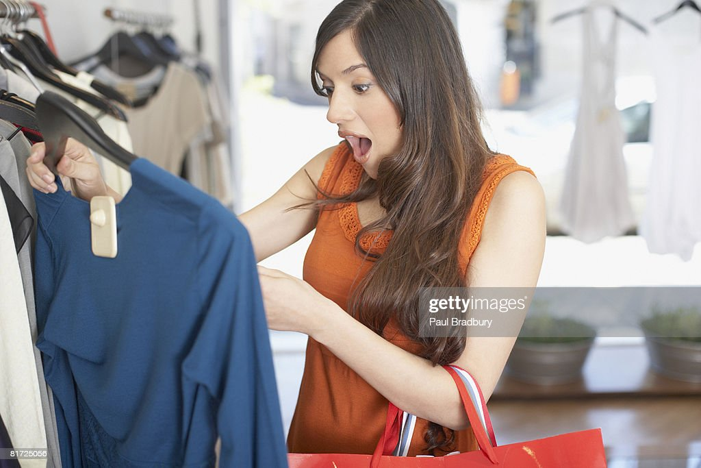 Woman in store looking at a shirt in shock : Stock Photo