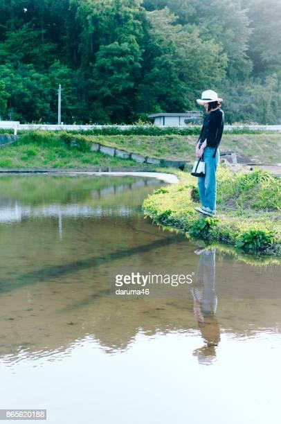 川沿いに立っている麦わら帽子の女性