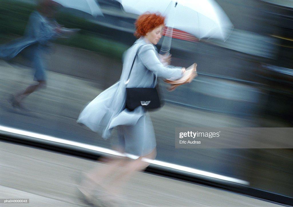 Woman in street holding umbrella, blurred : Stockfoto