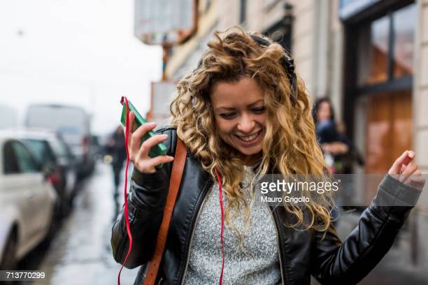 Woman in street listening to music through headphones