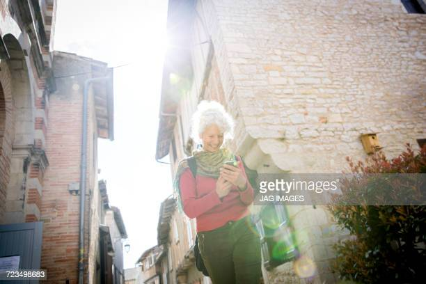 Woman in street looking at smartphone smiling. Bruniquel, France