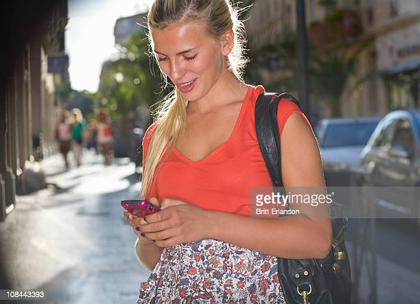 woman in street sends text on phone - nimes stock pictures, royalty-free photos & images