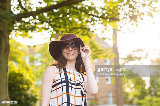 woman in street wearing sunglasses and floppy sunhat - drooping stock photos and pictures