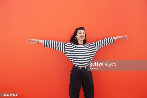 woman in striped top with arms outstretched, smiling. - luck stock pictures, royalty-free photos & images