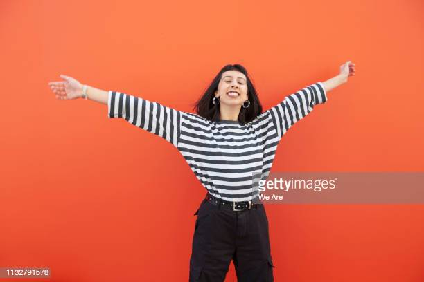 woman in striped top with arms outstretched, smiling. - colour block stock pictures, royalty-free photos & images