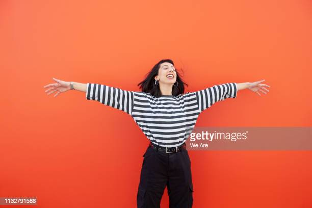 woman in striped top with arms outstretched, smiling. - ausgestreckte arme stock-fotos und bilder