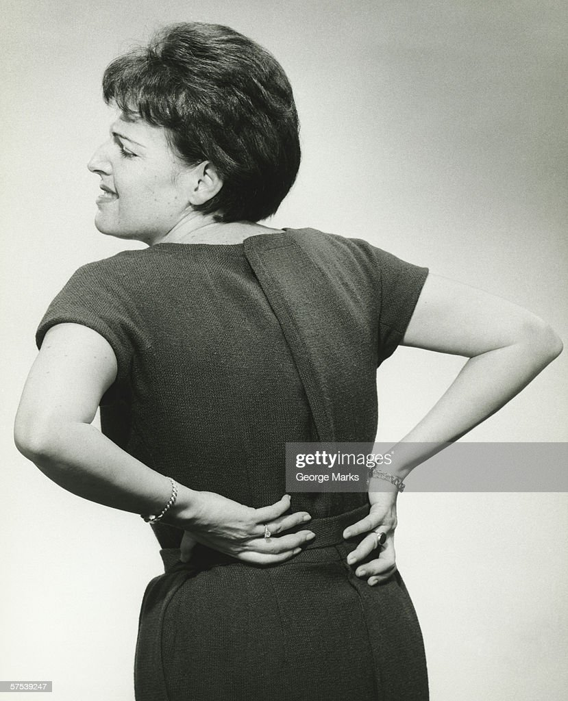 Woman in studio grasping back in pain, (B&W) : Stock Photo