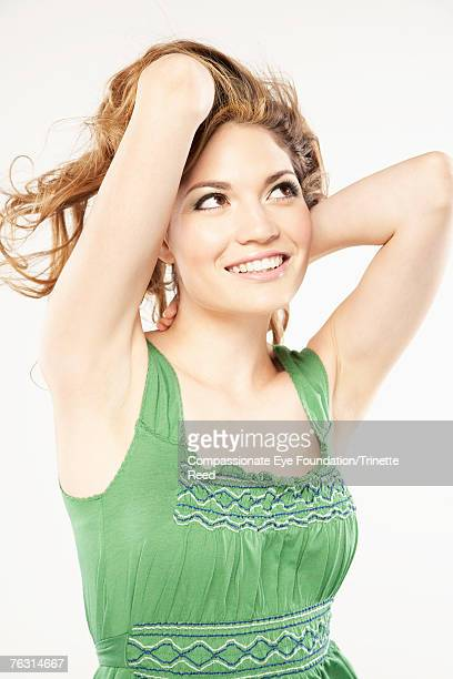 "woman in studio, smiling, hands in hair - ""compassionate eye"" stock-fotos und bilder"